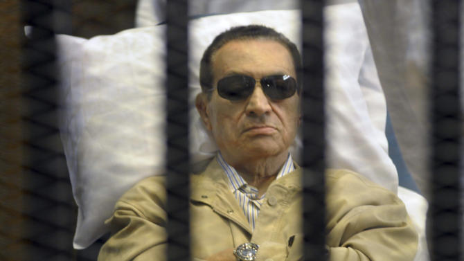 FILE - In this June 2, 2012 file photo, Egypt's ex-President Hosni Mubarak lies on a gurney inside a barred cage in the police academy courthouse in Cairo, during a hearing in which he was sentenced to life in prison for his role in the killing of protesters during the revolution in the spring of 2011. An Egyptian security official says Mubarak has been slipping in and out of consciousness, more than a week after he was transferred to a hospital inside a Cairo prison to serve his life sentence. The official says Mubarak's wife, former first lady Suzanne Mubarak, and her two daughters-in-law were visiting him in prison Sunday, June 10, 2012, after rumors circulated that he had died. (AP Photo, File)