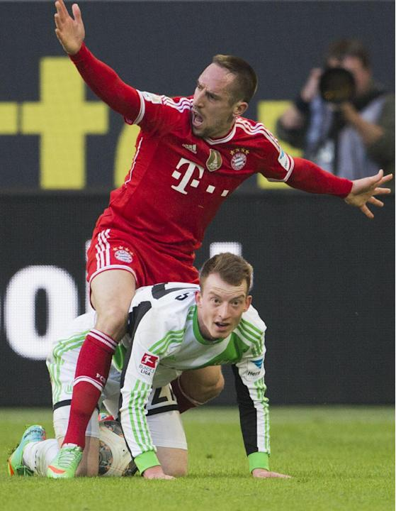 Bayern's Franck Ribery of France, top, and Wolfsburg's Maximilian Arnold, bottom, challenge for the ball during the German Bundesliga soccer match between VfL Wolfsburg and Bayern Munich inWol