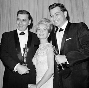 "FILE - In this April, 5,1965 file photo actress Debbie Reynolds poses with Academy awards winners for best music Richard M. Sherman, right and Robert Sherman, left, who received the award for Mary Poppins in Santa Monica Calif. Songwriter  Sherman, who wrote the tongue-twisting ""Supercalifragilisticexpialidocious"" and other enduring songs for Disney classics, has died. He was 86. (AP Photo,File)"