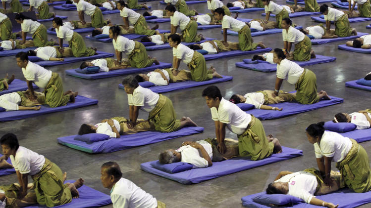 Thai masseuses perform mass massaging at a sport arena on the outskirts of Bangkok, Thailand Thursday, Aug. 30, 2012. Thailand has long been known as the massage capital of the world. Now, it has a Guinness World Record to prove it when some 641 massage therapists mass-massaged 641 people simultaneously for 12 minutes to win the honor Thursday at an indoor arena in Bangkok. The event was organized by the Health Ministry to promote the Southeast Asian nation's massage and spa industry. (AP Photo/Apichart Weerawong)