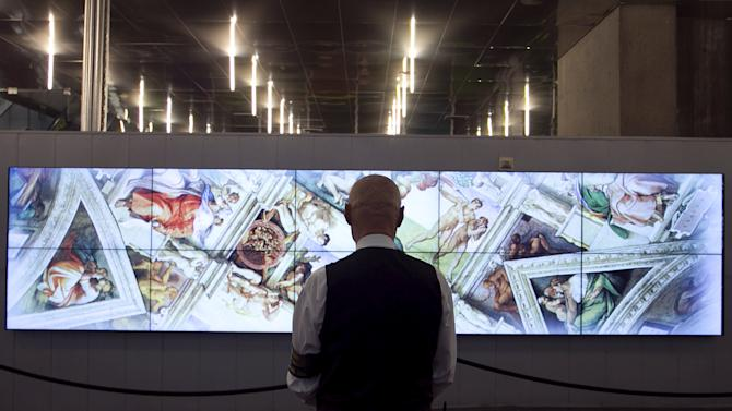 """A security guard in the Palais de Congress looks at a banner for the world premiere of """"Michelangelo's Sistine Chapel: The Exhibition"""" in Montreal"""