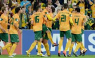 This file photo shows Australian players celebrating scoring a goal in their 2014 World Cup qualifying match against Japan, in Brisbane, in June. Australia has lined up a friendly against Lebanon in Beirut in the first senior international ever between the two nations, according to officials