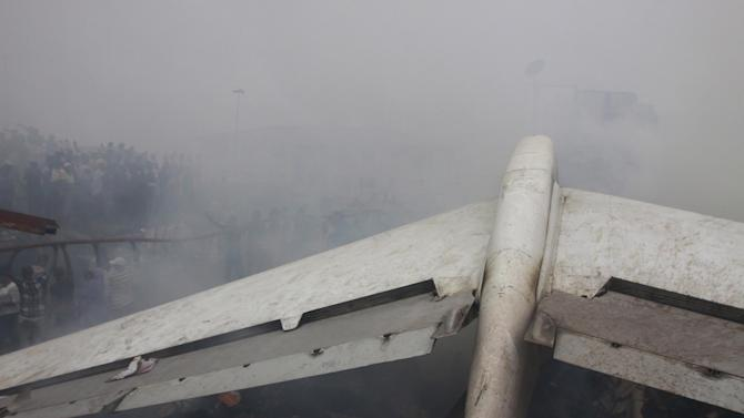 FILE- In this June. 3, 2012 file photo, smoke still rises at the site of a plane crash in Lagos, Nigeria,  Seven months after one of Dana Air planes crashed, killing at least 163 people, the Nigerian airline has resumed domestic flights in the West African nation. Dana Air sold tickets Thursday Jan. 3, 2013 for flights between Nigeria's capital, Abuja, and its largest city of Lagos. It was an Abuja-Lagos flight that crashed on June 3 in a densely populated neighborhood near Murtala Muhammed International Airport in Lagos, killing 153 people on board and at least 10 on the ground. (AP Photo/Sunday Alamba File)