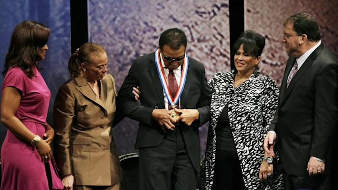 Retired boxing champion Muhammad Ali, center, is looks down at his Liberty Medal flanked by his daughter Laila Ali, from left, wife Lonnie Ali, sister-in-law Marilyn Williams and David Eisner, President and Chief Executive Officer of the National Constitution Center, looks on during a ceremony at the National Constitution Center, Thursday, Sept. 13, 2012, in Philadelphia. The honor is given annually to an individual who displays courage and conviction while striving to secure liberty for people worldwide. (AP Photo/Matt Slocum)