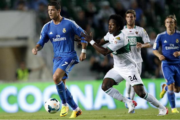 Real Madrid's Cristiano Ronaldo from Portugal drives the ball followed by Elche's  Carlos Alberto Sanchez Moreno  during their La Liga soccer match at the Martinez Valero stadium in Elche, Spain, Wedn