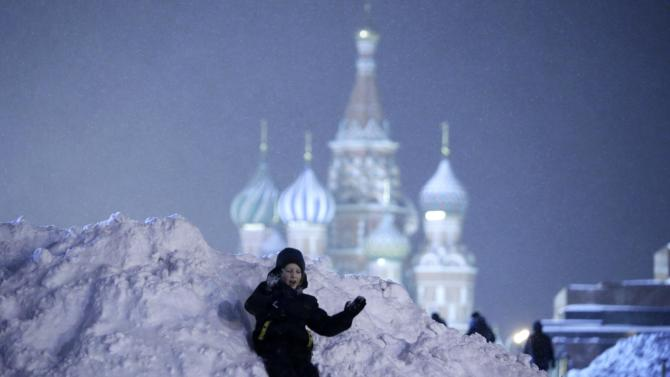 A boy slides from the top of a heap of snow in the Red Square in central Moscow