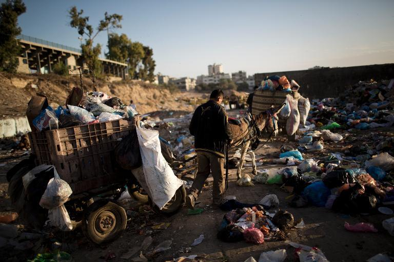Palestinian workers from the Gaza City municipality use a donkey cart to collect rubbish from the Yarmuk waste dump area, in Gaza City, on November 26, 2013