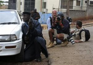 A policeman and photographers take cover after hearing gun shots near the Westgate shopping centre in Nairobi