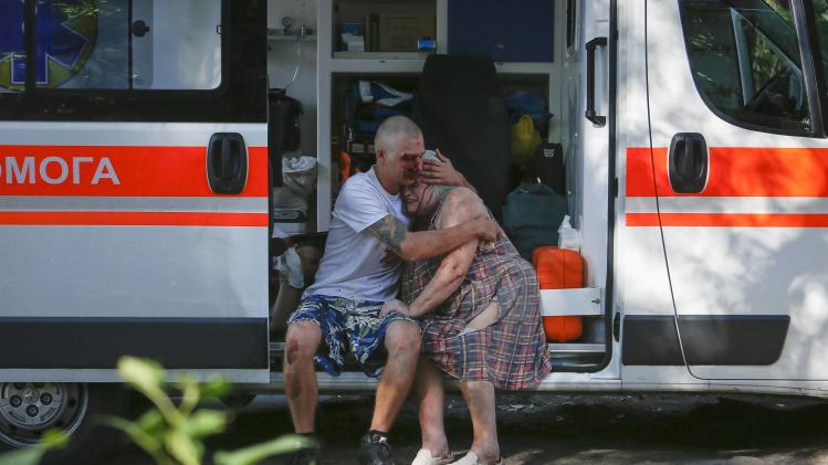 A man comforts a woman who were both wounded by what locals say was recent shelling by Ukrainian forces in Donetsk