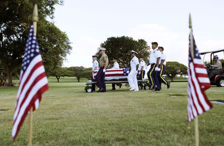 Remains of World War Two service members from the USS Oklahoma are disinterred so they can be identified during a Dignified Transfer ceremony at the National Memorial Cemetery of the Pacific in Honolulu, Hawaii