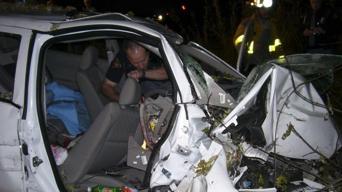 File photo of a police officer looking through the wreck of a 2005 Chevy Cobalt in St Croix County, Wisconsin