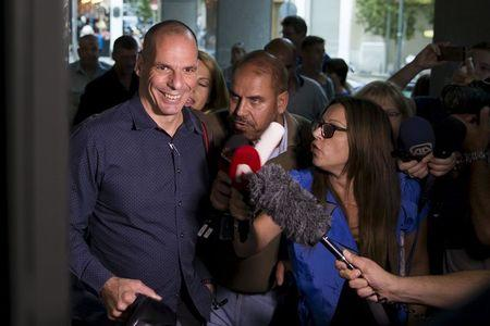 Greek Finance Minister Yanis Varoufakis is surrounded by the media as he leaves the Finance Ministry building in Athens