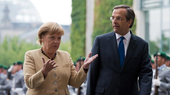 FILE - In this Aug. 24 2012 file picture  German Chancellor Angela Merkel, left, talks to Prime Minister of Greece Antonis Samaras, during a welcome ceremony at the chancellery in Berlin, Germany.  Germany's Chancellor Angela Merkel is to visit Greece next week as Athens works to convince its creditors to pay the next installment of its bailout package. Merkel's spokesman, Steffen Seibert, said the chancellor will meet Prime Minister Antonis Samaras in Athens on Tuesday.  Seibert said Friday Oct. 5, 2012  that Merkel's visit follows an invitation that Samaras made when he visited Berlin in August.  (AP Photo/dapd/Maja Hitij)
