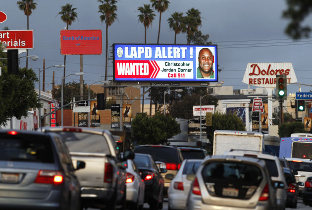 "A digital billboard along Santa Monica Boulevard on the west side of Los Angeles shows a ""wanted"" alert for former Los Angeles police officer Christopher Dorner Friday, Feb. 8, 2013.  Dorner is suspec"