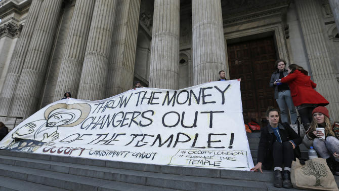 Activists of the Occupy hold a banner saying 'Throw the Money Makers out of the Temple' outside of St Paul's Cathedral  in London Sunday, Oct. 14, 2012. Several supporters of the anti-corporate Occupy movement chained themselves to the pulpit of St. Paul's Cathedral during a service on Sunday in an action marking the anniversary of its now-dismantled protest camp outside the London landmark. (AP Photo/Alastair Grant)