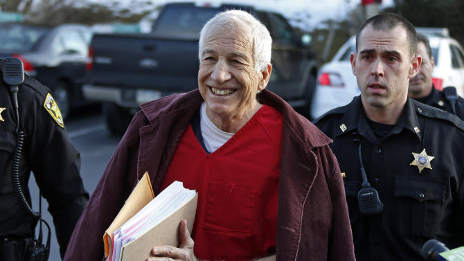 Former Penn State University assistant football coach Jerry Sandusky, center, arrives at the Centre County Courthouse for a post-sentence motion in Bellefonte, Pa., Thursday, Jan. 10, 2013. Thursday's hearing in Bellefonte is expected to delve into the legal challenges filed by Sandusky's lawyers, including their claim that a deluge of prosecution materials swamped the defense. Sandusky is serving a 30- to 60-year prison sentence after being convicted in June of 45 counts of child sexual abuse. (AP Photo/Gene J. Puskar)