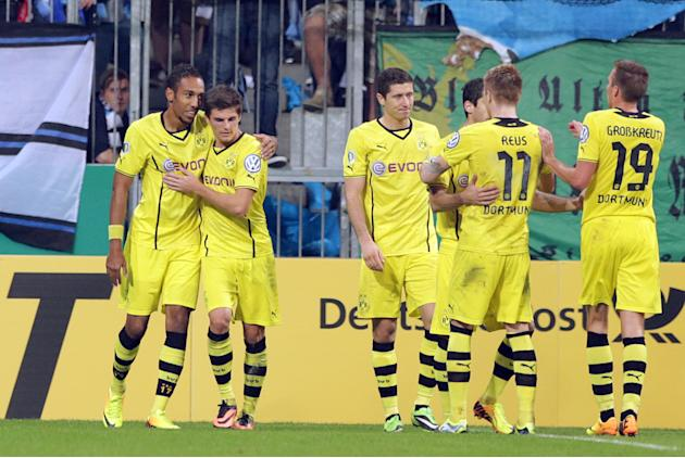 Dortmund's Pierre-Emerick Aubameyang of Gabon, left, celebrates with teammates after scoring his side's opening goal during the German soccer cup second round match between TSV 1860 Munich and Borussi