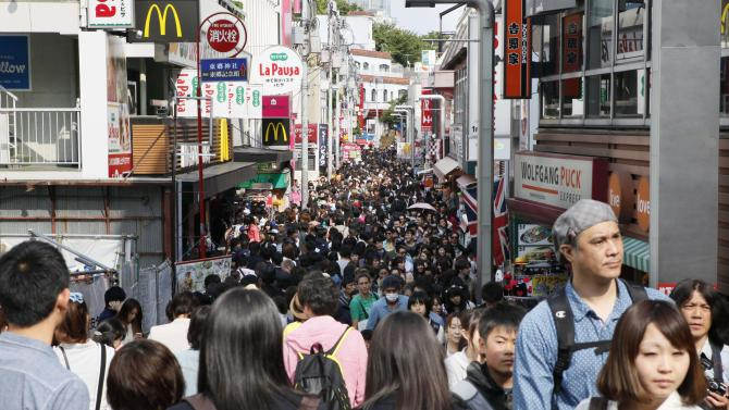 "In this photo taken Saturday, May 4, 2013, people walk at Takeshita street at Harajuku in Tokyo. Walk down the street packed with young people looking for latest ""kawaii (cute)"" trends. (AP Photo/Koji Sasahara)"