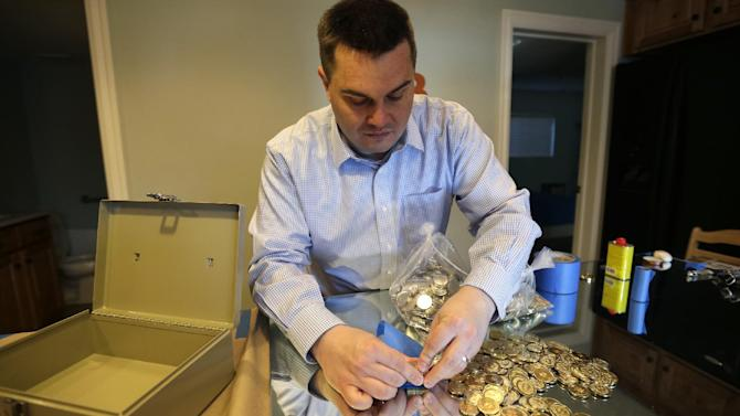 In this April 3, 2013 photo, Mike Caldwell, a 35-year-old software engineer, looks over bitcoin tokens at his shop in Sandy, Utah. Caldwell mints physical versions of bitcoins, cranking out homemade tokens with codes protected by tamper-proof holographic seals, a retro-futuristic kind of prepaid cash. With up to 70,000 transactions each day over the past month, bitcoins have been propelled from the world of Internet oddities to the cusp of mainstream use, a remarkable breakthrough for a currency which made its online debut only four years ago. (AP Photo/Rick Bowmer)