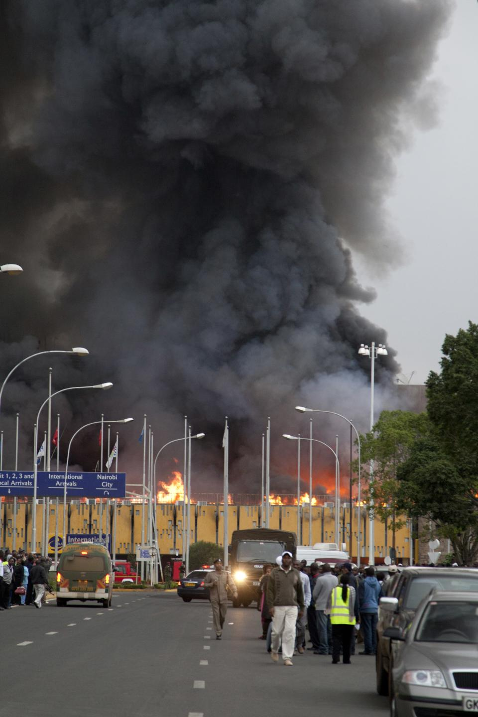 Black smoke billows from the Jomo Kenyatta International Airport in Nairobi, Kenya Wednesday, Aug. 7, 2013. The Kenya Airports Authority said the Kenya's main international airport has been closed until further notice so that emergency teams can battle the fire. (AP Photo/Sayyid Azim)