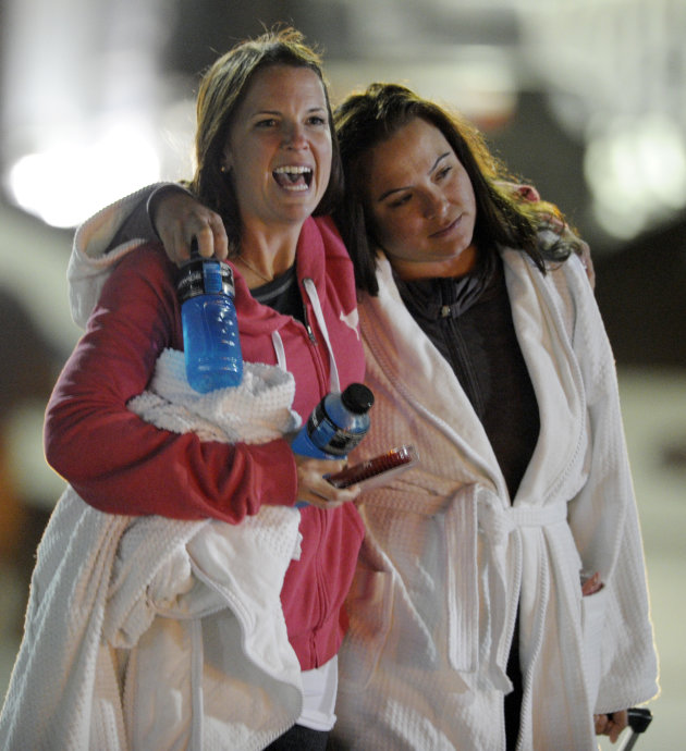 Kristina Courson, left, of Paris, Texas, is embraced by Jamie Hilliard, of Denison, Texas, after getting off the cruise ship Carnival Triumph in Mobile, Ala., Thursday, Feb. 14, 2013. The ship with mo