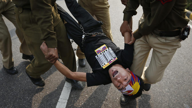 Indian policemen detain a Tibetan Youth Congress (TYC) supporter as he protests outside the Chinese Embassy in New Delhi, India, Monday, Nov. 12, 2012. TYC supporters shouted anti-Chinese government slogans outside the embassy to show support to Tibetans inside China who have set themselves on fire and protested against the Chinese government. (AP Photo/Saurabh Das)