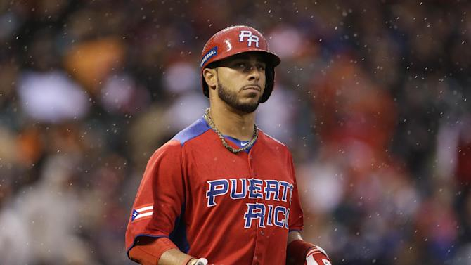 Puerto Rico's Mike Aviles runs in the rain after flying out against the Dominican Republic during the fourth inning of the championship2 game of the World Baseball Classic in San Francisco, Tuesday, March 19, 2013. (AP Photo/Eric Risberg)