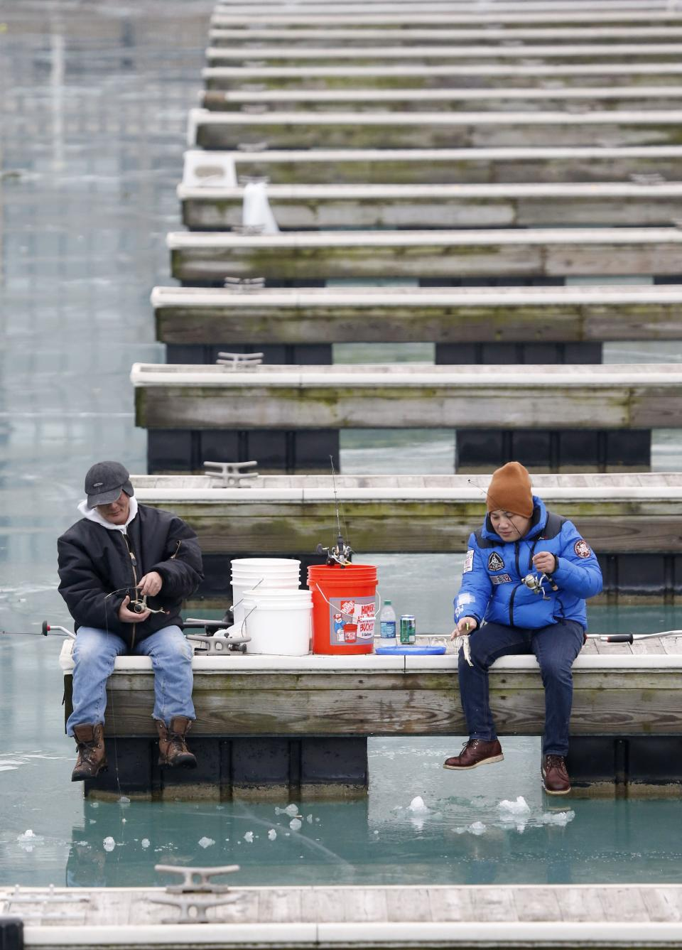 Despite unseasonably warm temperatures two men ice fish in Chicago's Belmont Harbor along Lake Michigan Tuesday, Jan. 29, 2013, in Chicago. Unseasonably warm temperatures broke records in the Chicago area with thunderstorm expected to usher in freezing temperatures and snow Wednesday. (AP Photo/Charles Rex Arbogast)