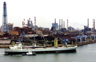 This file photo shows a freighter arriving at Kashima's main port with a metal factory seen in the background, on June 1, 2001. Japan's big manufacturers reduced greenhouse gas emissions by nearly 15 percent annually on average over the past five years compared to 1990, according to a survey published in the Nikkei daily