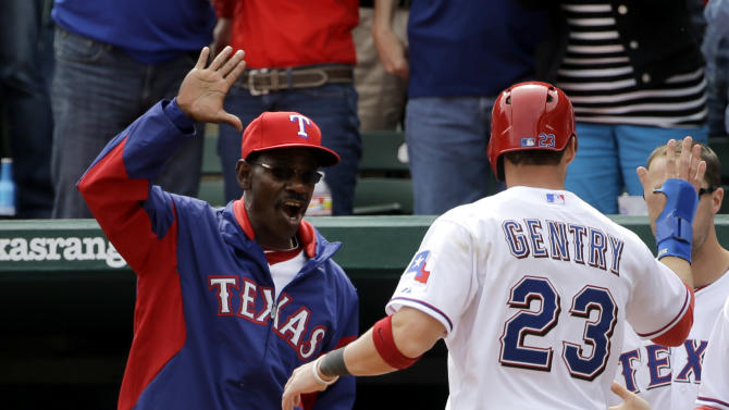 At the dugout, Texas Rangers manager Ron Washington left, greets Craig Gentry (23) who scored on an Ian Kinsler single to right in the eighth inning of a baseball game against the Los Angeles Angels, Friday, April 5, 2013, in Arlington, Texas. The Rangers won their home opener 3-2. (AP Photo/Tony Gutierrez)