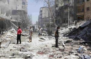 People inspect a site hit by what activists said was a barrel bomb dropped by forces loyal to Syria's President al-Assad in Aleppo
