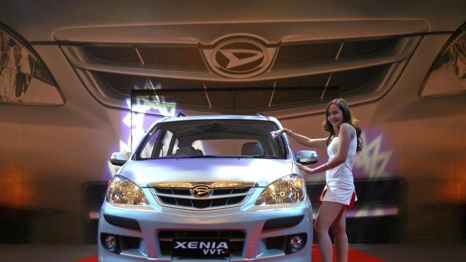File photo of a girl standing beside Daihatsu passenger car named Xenia during its launch in Jakarta