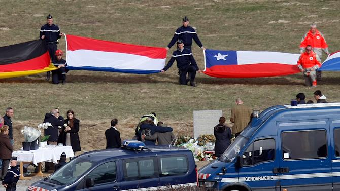 Flags representing differents nations are deployed during an homage ceremony with family members of victims, in front of a stele, a stone slab erected as a monument, set up in memory of the victims in the area where the Germanwings jetliner crashed in the French Alps, in Le Vernet, France, Sunday, March 29, 2015. The crash of Germanwings Flight 9525 into an Alpine mountain Tuesday killed all 150 people aboard, and has raised questions about the mental state of the co-pilot. Authorities believe the 27-year-old German deliberately sought to destroy the Airbus A320 as it flew from Barcelona to Duesseldorf. (AP Photo/Claude Paris)