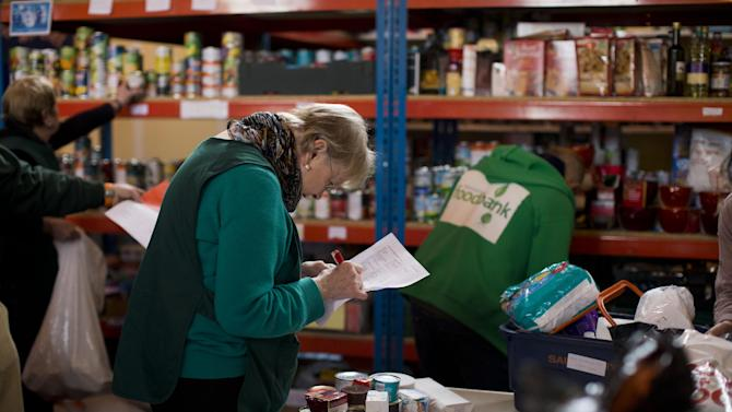 "In this photo taken Friday, April 5, 2013, volunteer Margaret Tobin checks items off a list of food to give out at a food bank in St Luke's Church in the West Norwood area of London, Friday, April 5, 2013. It's possible that official figures on first quarter economic growth, to be released Thursday, could put the country back in recession. It would take the smallest statistical variation to put the figure in negative territory which would place the country in recession, another recession _ the third since the 2008 financial crisis _ and is already being referred to with foreboding in the media as a ""Triple Dip"". (AP Photo/Matt Dunham)"