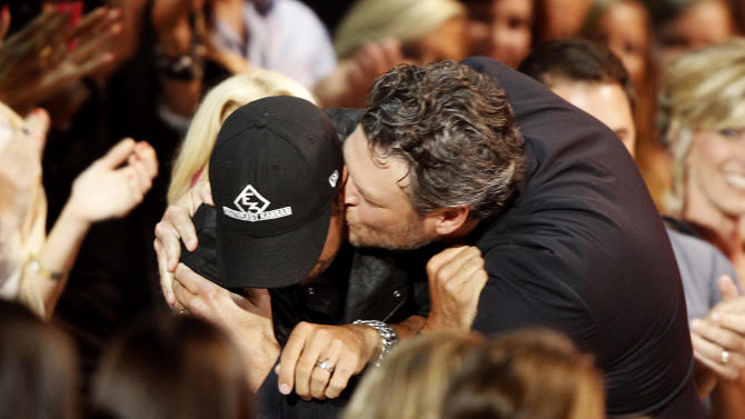 """Blake Shelton, right, kisses Luke Bryan in the audience as he walks to the stage to accept his award for male video of the year for """"Doin' What She Likes"""" at the CMT Music Awards at Bridgestone Arena on Wednesday, June 4, 2014, in Nashville, Tenn. (Photo by Wade Payne/Invision/AP)"""