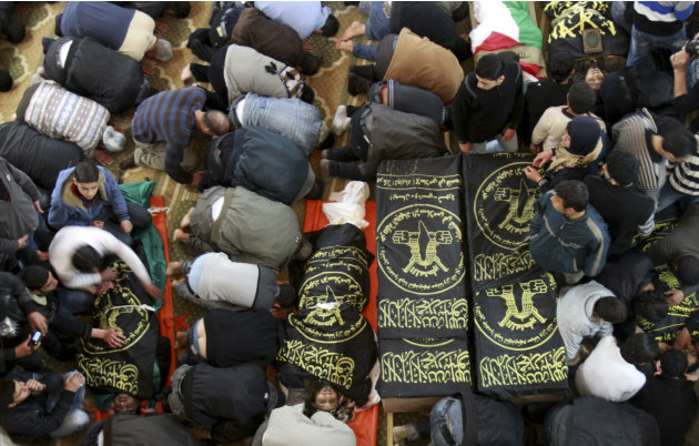 Palestinians mourn next to the bodies of Islamic Jihad militants during their funerals in Gaza City, Saturday, March 10, 2012. The worst violence between Israel and the Gaza Strip in nearly a year ent