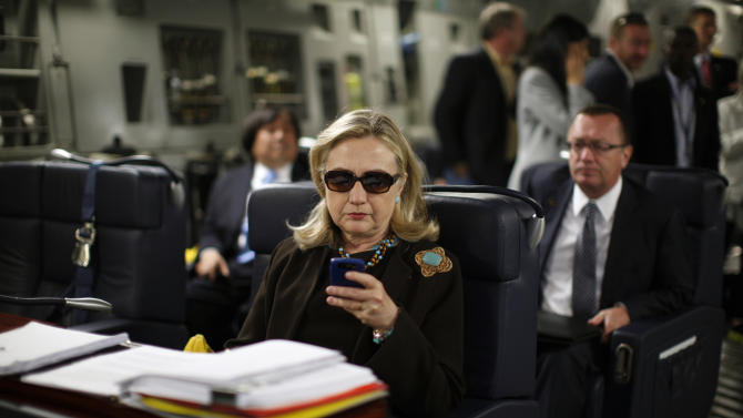 """FILE - In this Oct. 18, 2011, file photo, then-Secretary of State Hillary Rodham Clinton works from a desk inside a C-17 military plane upon her departure from Malta, in the Mediterranean Sea, bound for Tripoli, Libya. Clinton has joined Twitter, describing herself as a """"pantsuit aficionado"""" and a """"hair icon."""" The potential 2016 presidential candidate's profile page shows the infamous photo of the stern-looking Clinton wearing dark sunglasses and reading her Blackberry. (AP Photo / Kevin Lamarque, Pool, File)"""