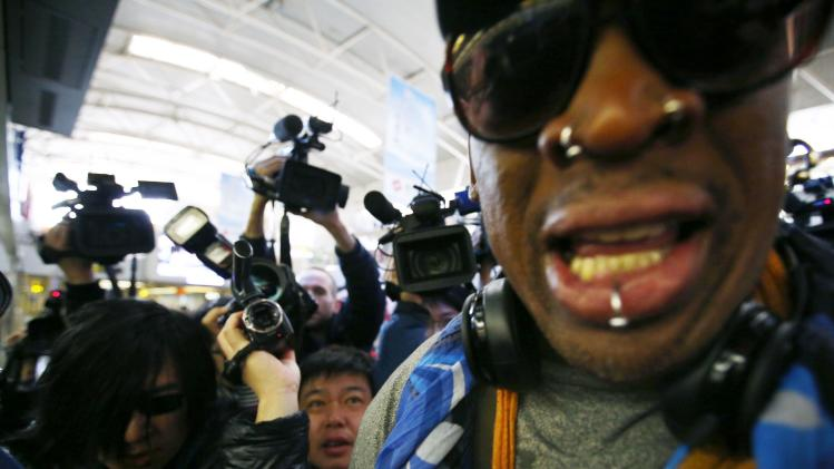 Former NBA basketball player Dennis Rodman is surrounded by the media at Beijing International Airport before he leaves for Pyongyang