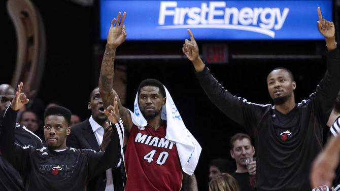 Miami Heat's Norris Cole, left, Udonis Haslem (40) and Rashard Lewis, right, celebrate from the bench in the second half of an NBA basketball game against the Cleveland Cavaliers on Wednesday, March 20, 2013, in Cleveland. Miami won 98-95. (AP Photo/Tony Dejak)