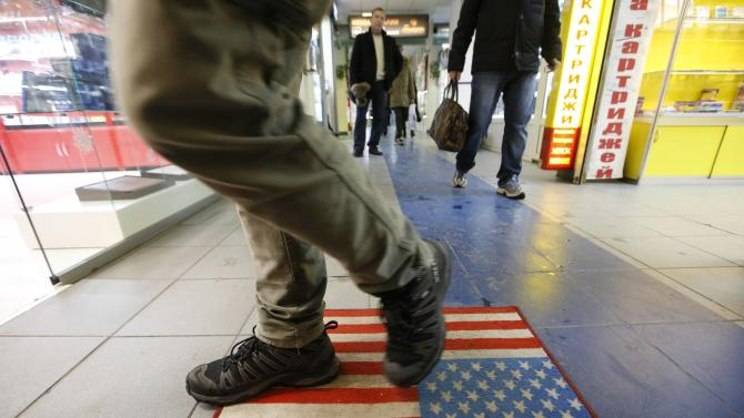 A man steps on a footcloth styled on a U.S. flag inside a shopping centre in Moscow