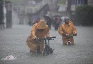 Two men push their bikes along a flooded area in Rizal, east of Manila, Philippines on Tuesday Aug. 7, 2012. Torrential rains pounding the Philippine capital on Tuesday paralyzed traffic as waist-deep floods triggered evacuations of tens of thousands of residents and the government suspended work in offices and schools.(AP Photo/John Javellana)