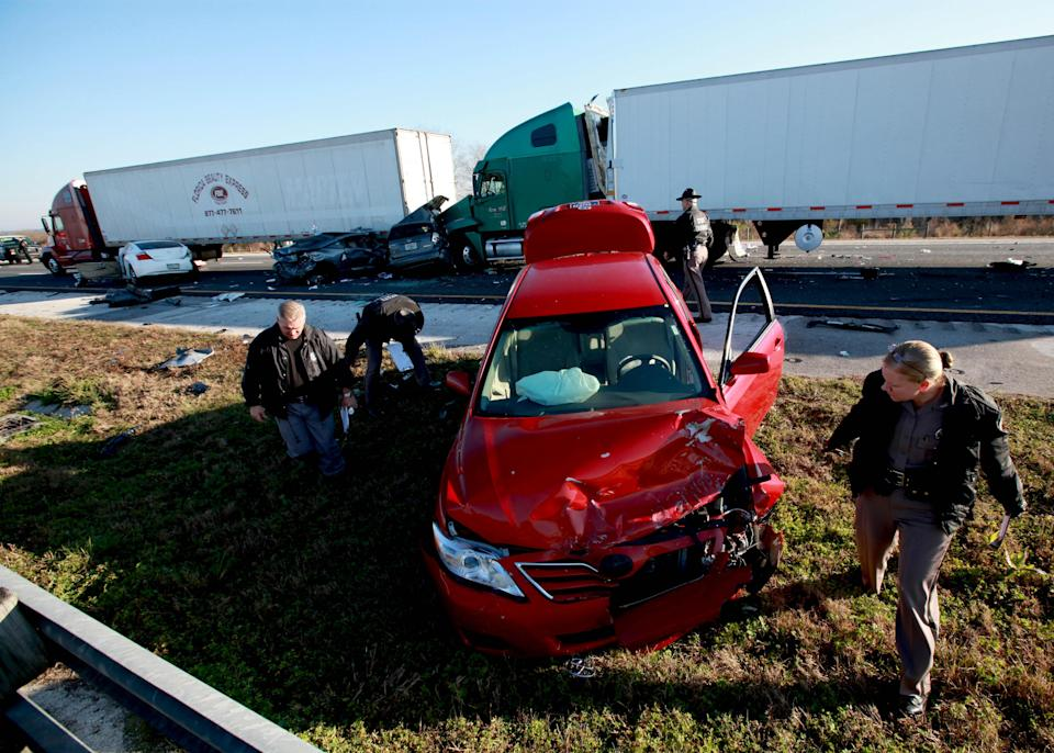 Officials work at the scene of a multi-vehicle wreck on Interstate 75 at Paynes Prairie on Sunday, Jan. 29, 2012, south of Gainesville, Fla.  (AP Photo/Matt Stamey, The Gainesville Sun)