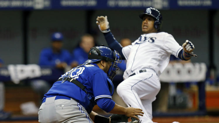 Toronto Blue Jays catcher Dioner Navarro waits for the throw as Tampa Bay Rays' Yunel Escobar slides in safely to score during the sixth inning of a baseball game Saturday, July 12, 2014, in St. Petersburg, Fla. (AP Photo/Mike Carlson)