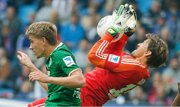 Bremen's Nils Petersen , left, and Hamburg 's goalie  Rene Adler challenge for the ball during the German Bundesliga soccer match between SV Hamburg and SV Werder Bremen in Hamburg, northern Germany S