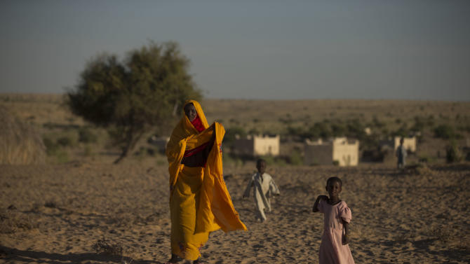 In this Nov. 1, 2012 photo, 7-year-old Achta, right, walks with her mother Fatme Ousmane in the village of Louri in the Mao region of Chad. Achta's birth seven years ago coincided with the first major drought to hit the Sahel this decade. Climate change has meant that the normally once-a-decade droughts are now coming every few years. The droughts decimated her family's herd. With each dead animal, they ate less. (AP Photo/Rebecca Blackwell)