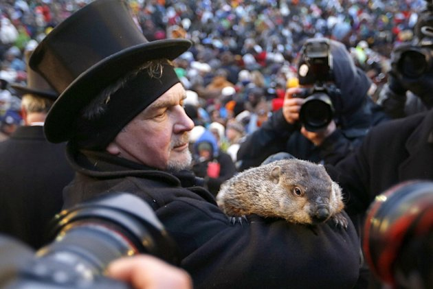 Groundhog Club Co-handler John Griffiths holds the weather predicting groundhog, Punxsutawney Phil, as he is surrounded by photographers after the club said Phil did not see his shadow and there will