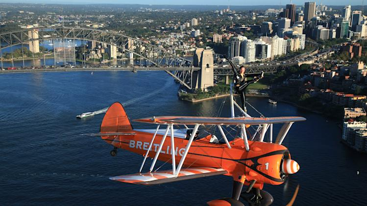 DISTRIBUTED FOR BREITLING - Breitling Wingwalker Sarah Tanner, from the UK, performs over Sydney Harbour in what is the first visit to the southern hemisphere by the UK based Breitling Wingwalker team in Sydney, Australia, on Thursday, March 7, 2013. The Stearman biplane, piloted by Martyn Carrington, performed an aerial display in front of the iconic Sydney Opera House and Sydney Harbour Bridge. (Michael Jorgensen for Breitling via AP Images)