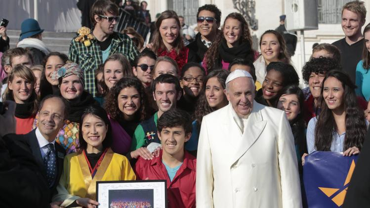 "Pope Francis poses with members of musical group ""Up with People"" during his Wednesday general audience in Saint Peter's square at the Vatican"
