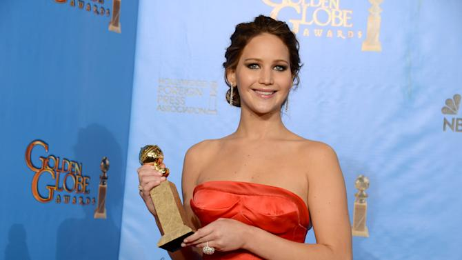 """Jennifer Lawrence poses with the award for best performance by an actress in a motion picture comedy or musical for """"Silver Linings Playbook"""" backstage at the 70th Annual Golden Globe Awards at the Beverly Hilton Hotel on Sunday Jan. 13, 2013, in Beverly Hills, Calif. (Photo by Jordan Strauss/Invision/AP)"""