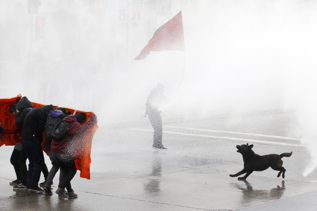 Student protesters are hit by a jet of water as they clash with riot policemen during a demonstration against the government in Santiago
